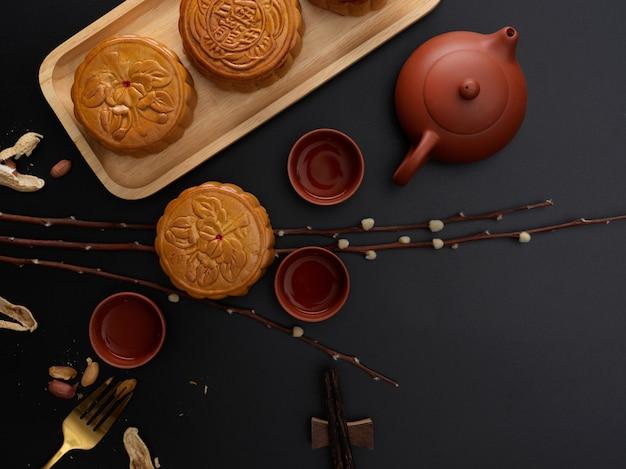 Bovenaanzicht van de instelling van de tabel met traditionele maancakes, theeservies, decoratie en kopie ruimte. chinees karakter op de maancake vertegenwoordigt