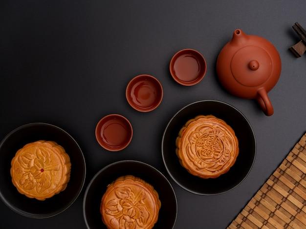 Bovenaanzicht van de instelling van de zwarte tafel met traditionele maancakes, theeservies en kopie ruimte