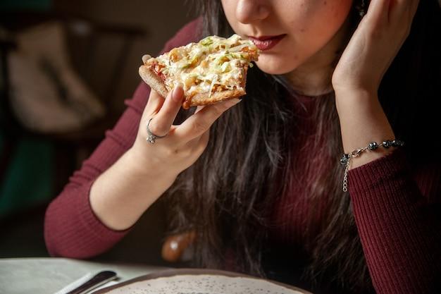 Bovenaanzicht van de jonge vrouw die een plak van heerlijke pizza eet, consumeert fastfood