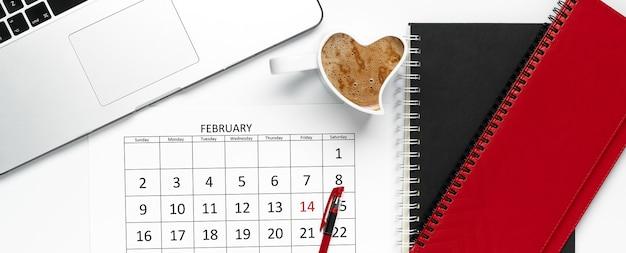Bovenaanzicht van de kalender van februari-pagina met pen erop, blocnotes, kopje koffie en laptop.