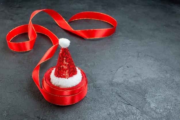 Bovenaanzicht van de kerstman hoed op een rol lint aan de rechterkant op donkere achtergrond