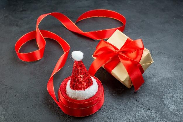 Bovenaanzicht van de kerstman hoed op een rol lint en mooi cadeau op donkere achtergrond