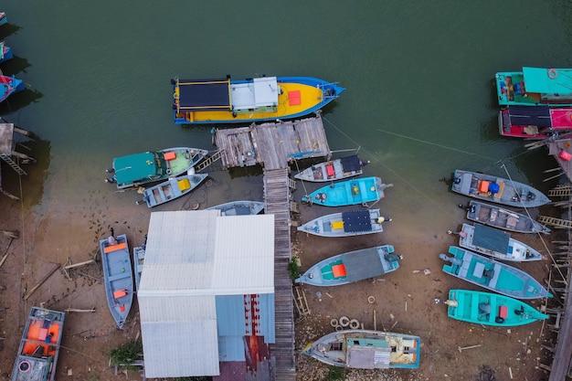 Bovenaanzicht van de kleine boten op de oever van het meer en een oude houten pier