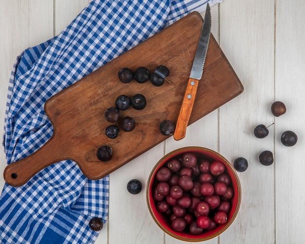 Bovenaanzicht van de kleine zure blauw-zwarte sleepruimen op een houten keukenplank met mes met rode kersen op een rode kom op een grijze houten achtergrond