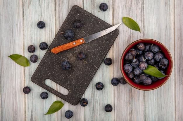 Bovenaanzicht van de kleine zure blauw-zwarte sleepruimen op een kom met sleepruimen geïsoleerd op de keukenplank met mes snijden op een grijze houten achtergrond
