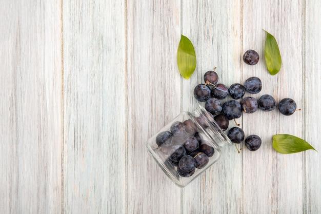 Bovenaanzicht van de kleine zure blauw-zwarte sleepruimen vallen uit een glazen pot met bladeren op een grijze houten achtergrond met kopie ruimte