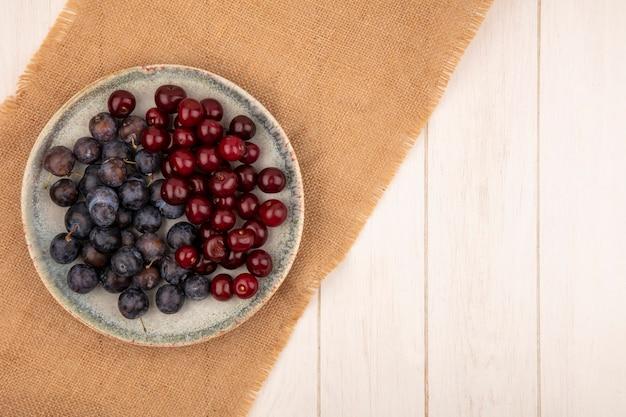 Bovenaanzicht van de kleine zure blauwzwarte fruit sleepruimen met rode kersen op een bord op een zakdoek op een witte achtergrond met kopie ruimte