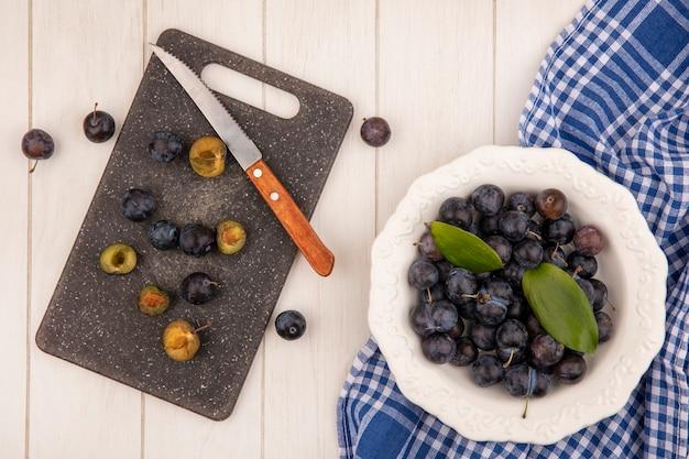 Bovenaanzicht van de kleine zure blauwzwarte fruit sleepruimen op een kom met plakjes sleepruimen op een keuken snijplank met mes op een witte achtergrond