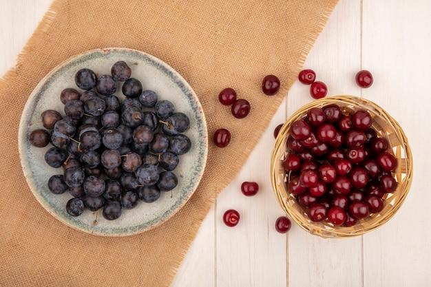 Bovenaanzicht van de kleine zure blauwzwarte fruit sleepruimen op een kom op een zakdoek met rode kersen op een emmer op een witte achtergrond