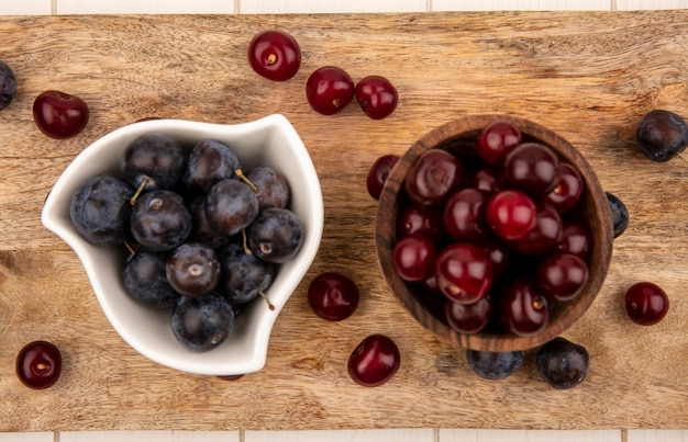 Bovenaanzicht van de kleine zure blauwzwarte fruit sleepruimen op een witte kom met rode kersen op een houten kom op een houten keukenbord op een witte achtergrond
