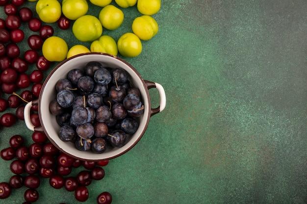 Bovenaanzicht van de kleine zure blauwzwarte fruitslaes op een kom met groene kersenpruim op een groene achtergrond met kopie ruimte
