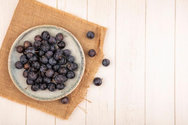 Bovenaanzicht van de kleine zure blauwzwarte fruitslaes op een kom op een zakdoek op een witte achtergrond met kopie ruimte