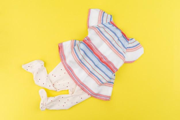 Bovenaanzicht van de kleren van het babymeisje op gele achtergrond