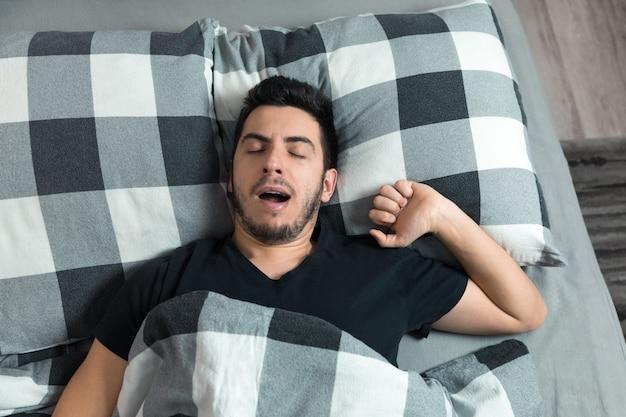 Bovenaanzicht van de knappe man gaapt en wrijft in zijn ogen terwijl hij in bed slaapt.