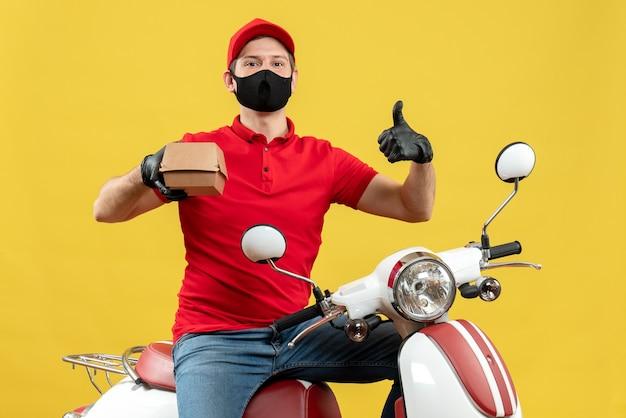 Bovenaanzicht van de koerier man met rode blouse en hoed handschoenen in medische masker zittend op de scooter houden volgorde met duim omhoog