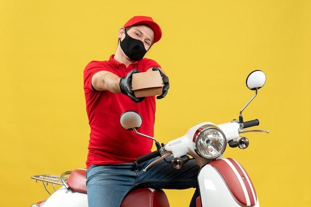 Bovenaanzicht van de koerier man met rode blouse en hoed handschoenen in medische masker zittend op scooter bevel geven