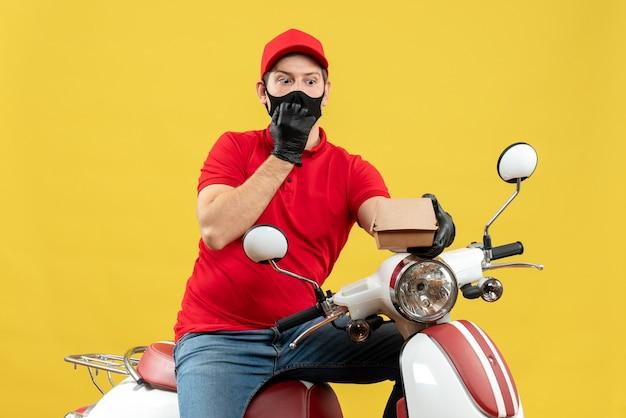 Bovenaanzicht van de koerier man met rode blouse en muts handschoenen in medische masker zittend op scooter holding order verrast gevoel
