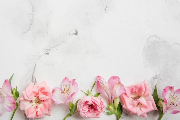 Bovenaanzicht van de lente rozen en orchideeën met marmeren achtergrond en kopie ruimte