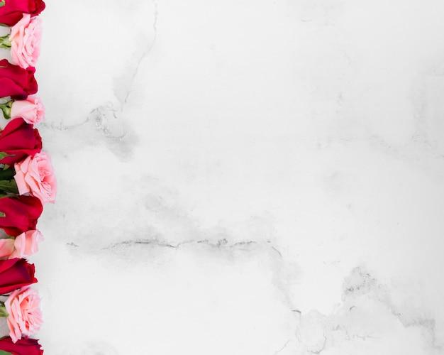 Bovenaanzicht van de lente rozen met marmeren achtergrond en kopie ruimte