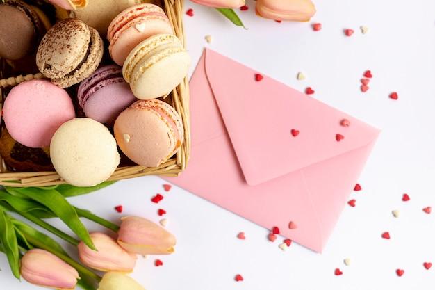 Bovenaanzicht van de mand macarons en envelop voor valentijnsdag