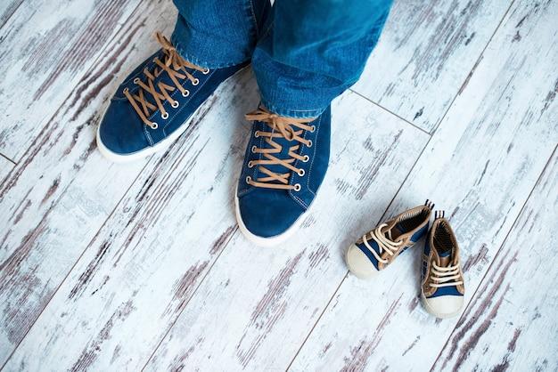 Bovenaanzicht van de papa's en de babysneakers op de houten vloer