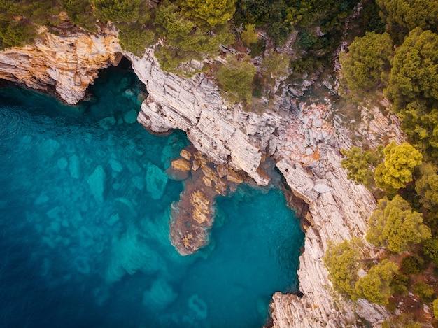 Bovenaanzicht van de rotsachtige kust van de kristalheldere adriatische zee, drone shot