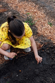 Bovenaanzicht van de rug een meisje in een gele jurk zit gehurkt en plant groentezaden in de zwarte...