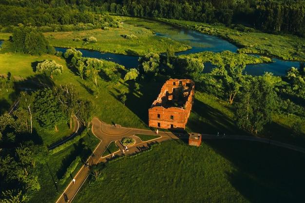 Bovenaanzicht van de ruïnes van een oude molen in loshitsky park in minsk en de rivier svisloch bij zonsondergang. prachtige natuur van wit-rusland.