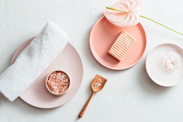 Bovenaanzicht van de spa-omgeving met zeep, handdoek, zout en bloem op witte achtergrond
