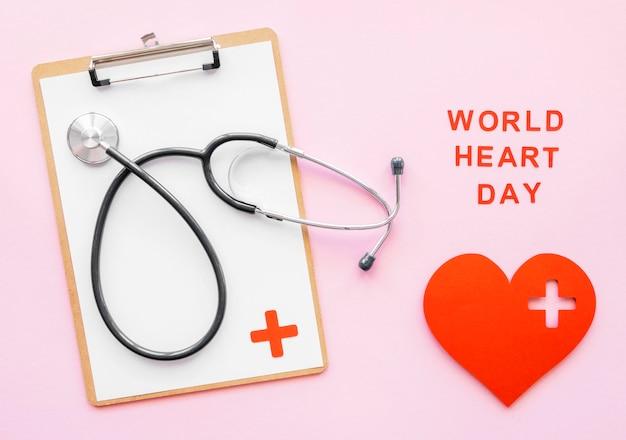 Bovenaanzicht van de stethoscoop met kladblok en papier hart