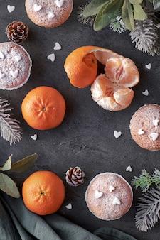 Bovenaanzicht van de tafel met satsuma's, suikerstroop muffins en kerststerren cookies op donker