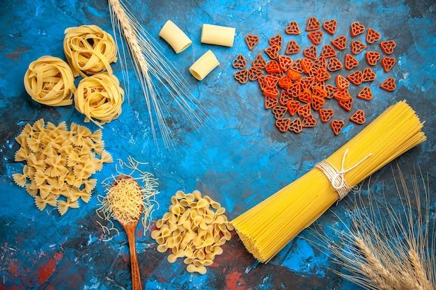 Bovenaanzicht van de voorbereiding van het diner met pasta noedels op blauwe achtergrond