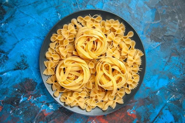 Bovenaanzicht van de voorbereiding van het diner met pasta noedels op een zwarte plaat op blauwe achtergrond