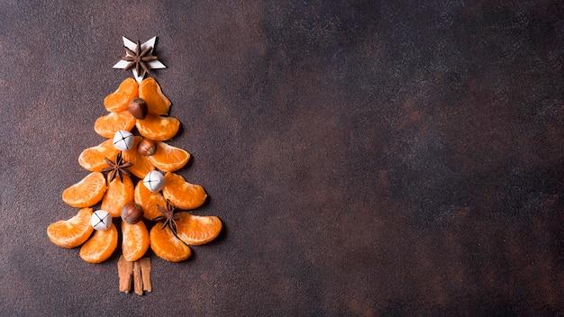 Bovenaanzicht van de vorm van een kerstboom gemaakt van mandarijnen met kopie ruimte