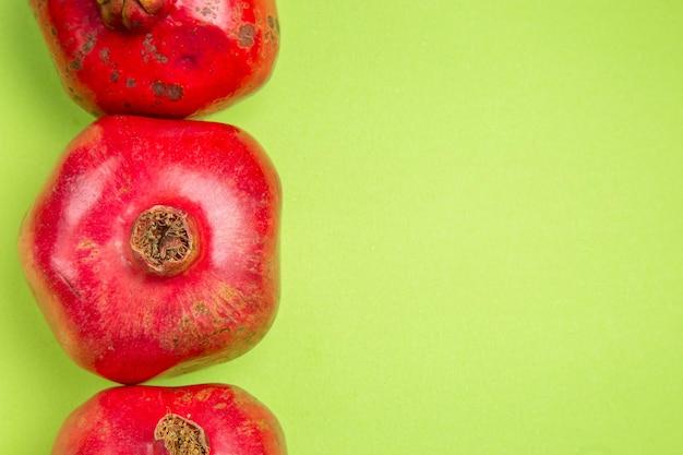 Bovenaanzicht van de vruchten drie rode granaatappels aan de linkerkant van de groene tafel