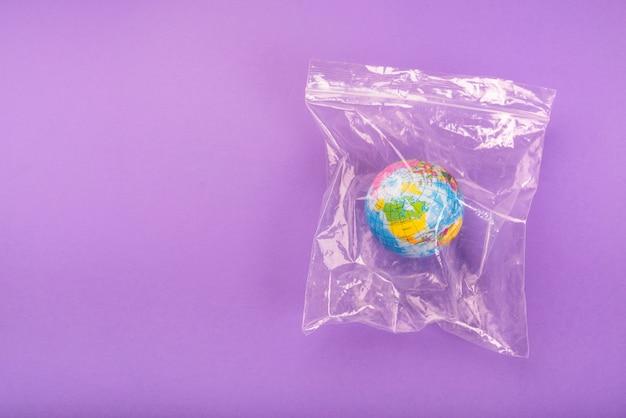 Bovenaanzicht van de wereld in zip lock plastic zak over paarse achtergrond