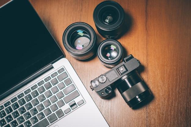 Bovenaanzicht van de werkplek, camera, lenzen en computer van de fotograaf