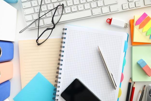 Bovenaanzicht van de werkplek. notitieblok openen en zilveren pen. zwarte glazen. wit modern toetsenbord op desktop. details voor werk. kantoorbenodigdheden en creativiteit concept