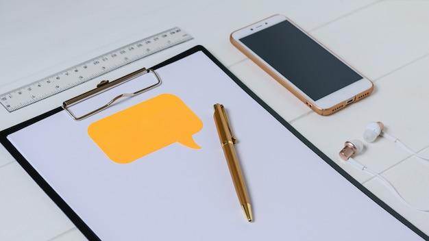 Bovenaanzicht van de werkplek van de ontwerper met smartphone, tablet, hoofdtelefoon en pen