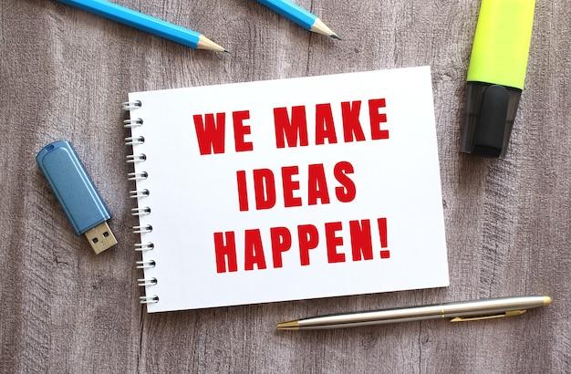 Bovenaanzicht van de werkruimte. kladblok met we make ideas happen tekst, pen, potloden, flashstation op grijze houten tafel. bedrijfsconcept.
