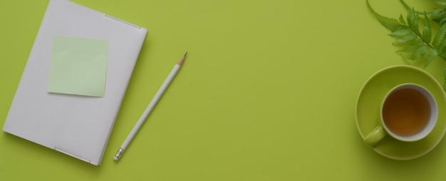 Bovenaanzicht van de werkruimte met dagboek notebook, kopje thee, decoratie en kopie ruimte op groene tafel