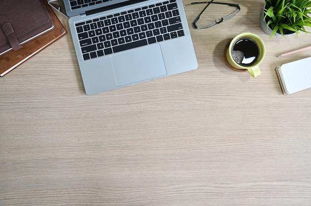Bovenaanzicht van de werkruimte met laptopcomputer, koffie, glazen, boeken en plantendecoratie op kantoor houten tafel.
