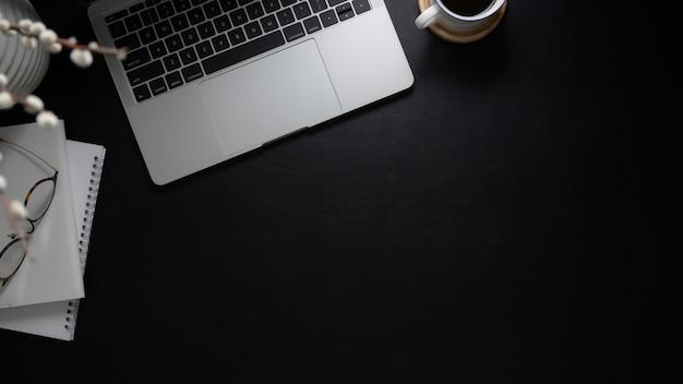 Bovenaanzicht van de werkruimte met laptopcomputer, notebooks, bril, koffiekopje