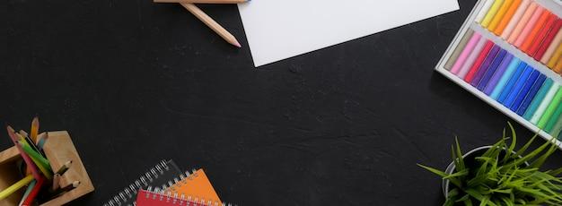 Bovenaanzicht van de werkruimte van de kunstenaar met schetspapier, oliepastels, tekengereedschappen en kopieerruimte
