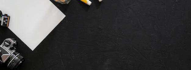 Bovenaanzicht van de werkruimte van de kunstenaar met schetspapier, tekengereedschappen, camera en kopieerruimte