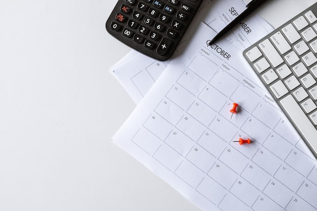 Bovenaanzicht van de werkruimte van het bureau met koffiekopje, toetsenbord en werkschema op witte tabelachtergrond. plat leggen