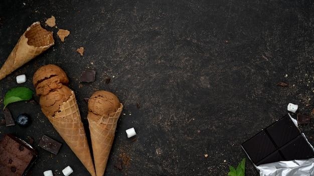 Bovenaanzicht van de zomer dessert met chocoladearoma ijshoorntjes op donkere tafel