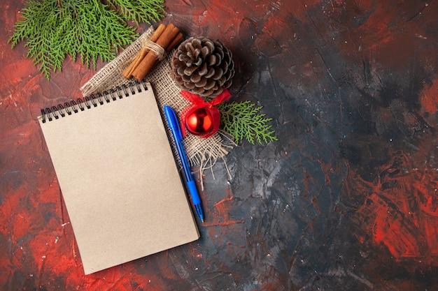 Bovenaanzicht van decoratie accessoires conifer kegel spar takken kaneel limoenen en notebook op donkere achtergrond