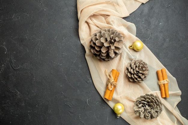 Bovenaanzicht van decoratie-accessoires van kaneellimoenen en drie coniferen op nudekleurige handdoek op zwarte kleurachtergrond