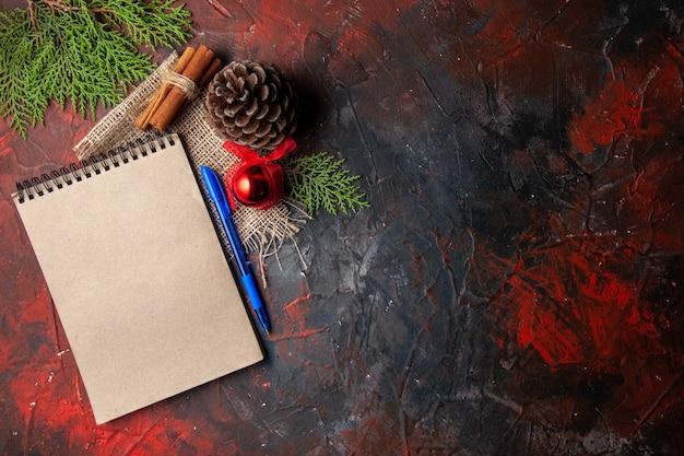 Bovenaanzicht van decoratieaccessoires conifer kegel spar takken kaneel limoenen en notitieboekje op donkere achtergrond